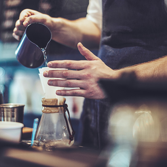 Barista preparing filter coffee to depict commercial combined insurance by Find Insurance NI