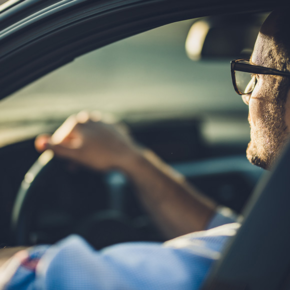 Man in glasses driving car to depict motor insurance by Find Insurance NI