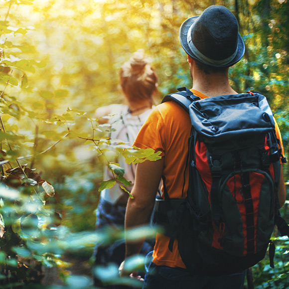 Travellers walking through woods to depict travel insurance by Find Insurance NI